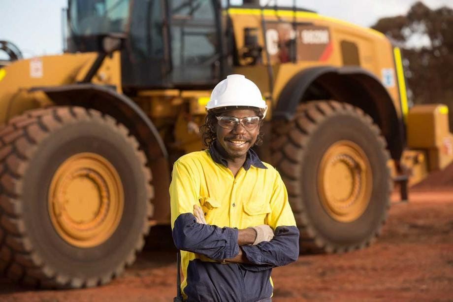 Workman standing in front of mining machinery
