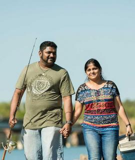 Couple walking along peer with fishing rod