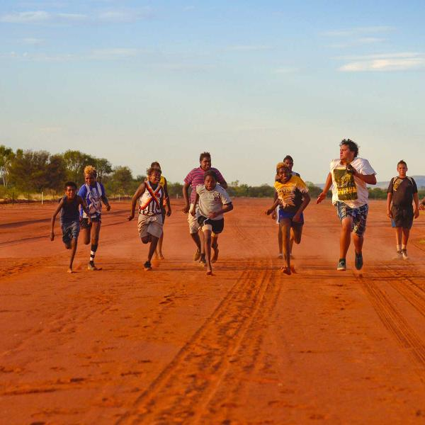 Children running a race on a red dust road