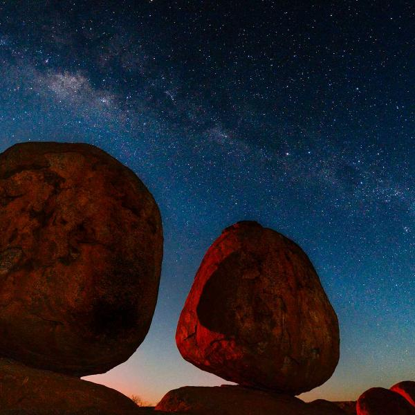 Devils Marbles at night with the sun setting and stars in the background