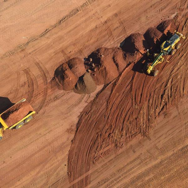 Aerial view of a grader and truck working on earthworks