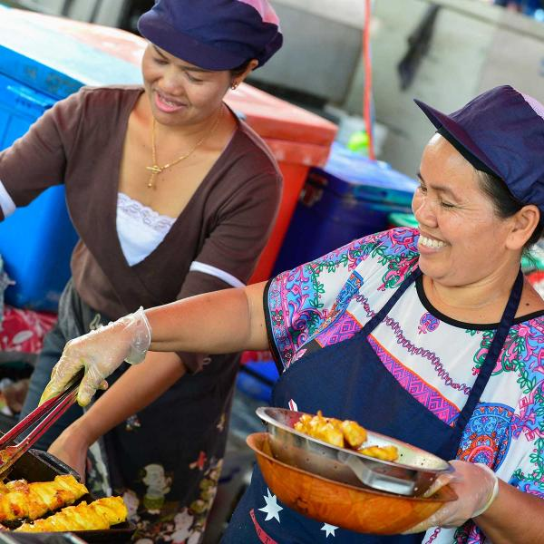 Two women serving food in a market stall