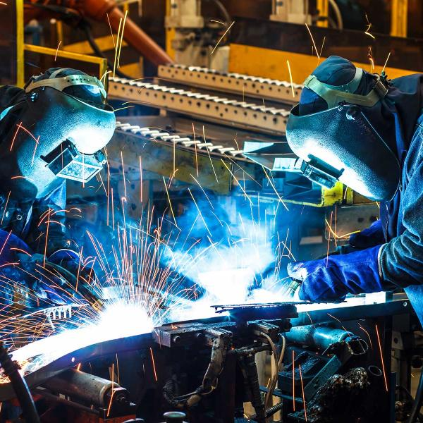 Two men welding in a workshop