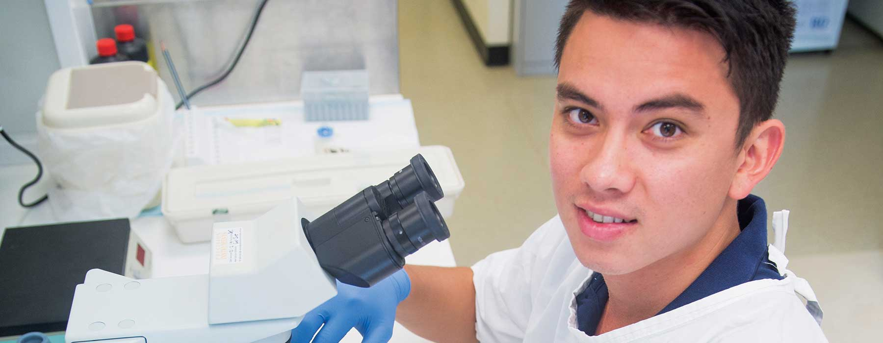 Student in lab working with microscope