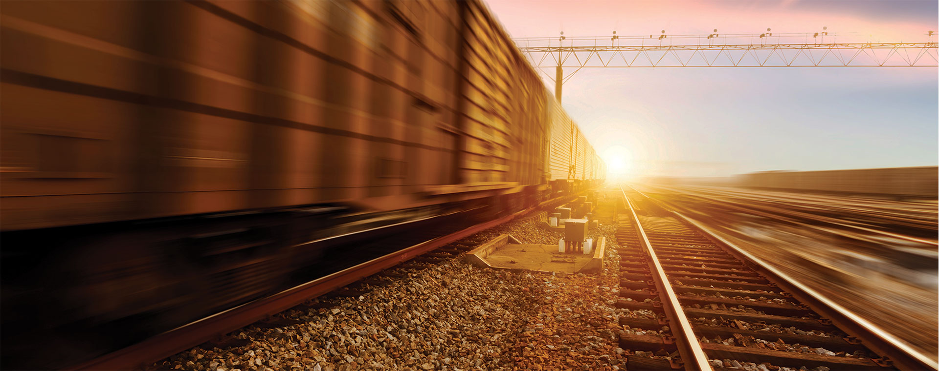 Train on a track with sun setting in the background
