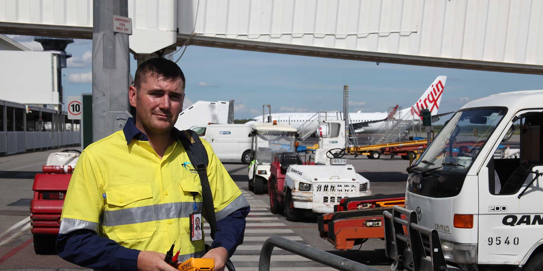 Workman standing beside vehicles at airport